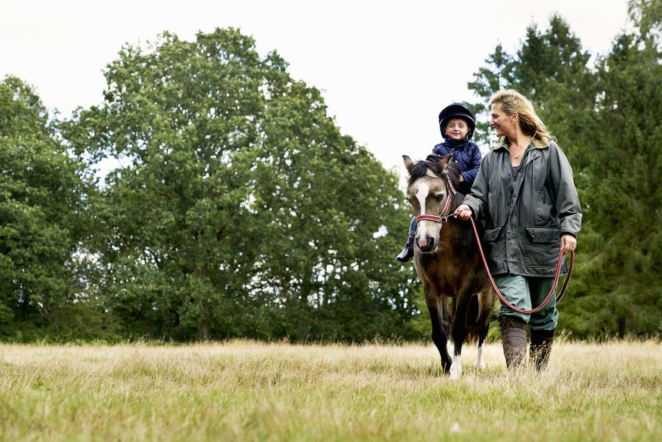 Mother leading horse riding son in field