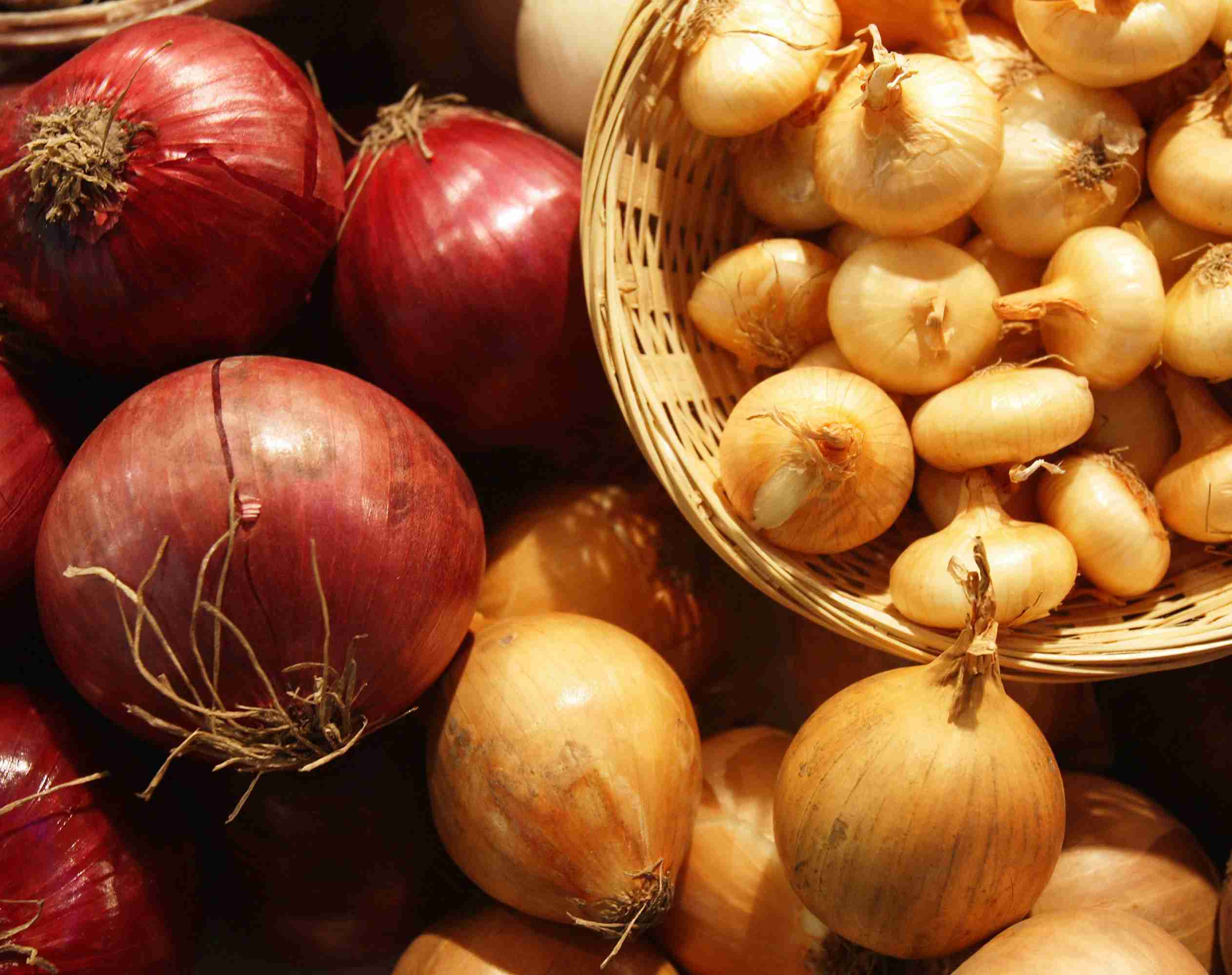 A variety of red and yellow onions, with the yellow ones in a basket.