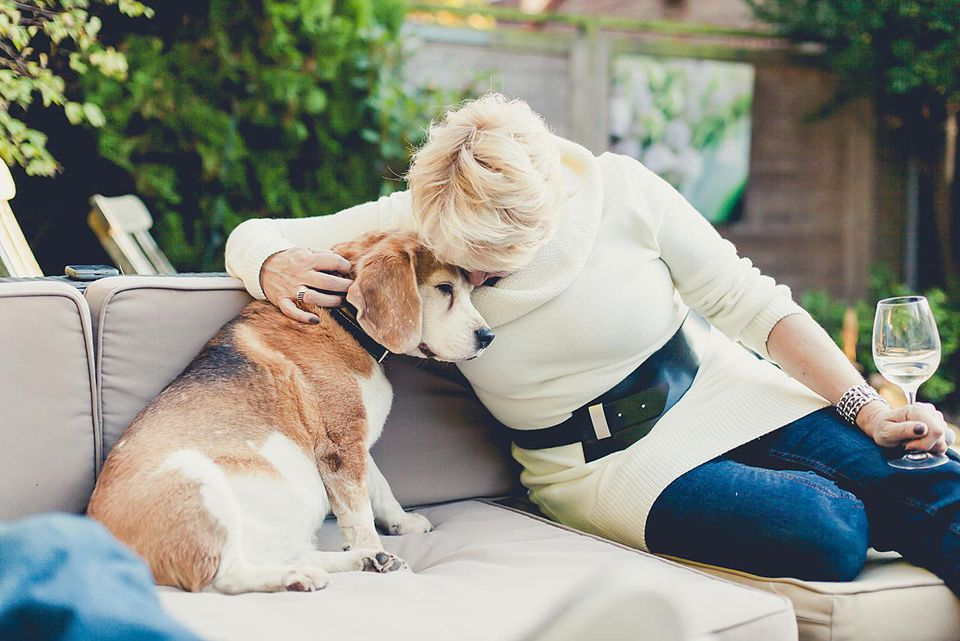 A woman cuddling a beagle, while sitting on a sofa in the garden and holding a glass of white wine