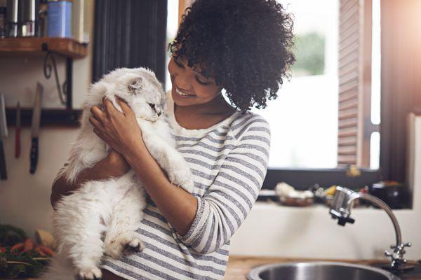 Woman cuddles cat in kitchen
