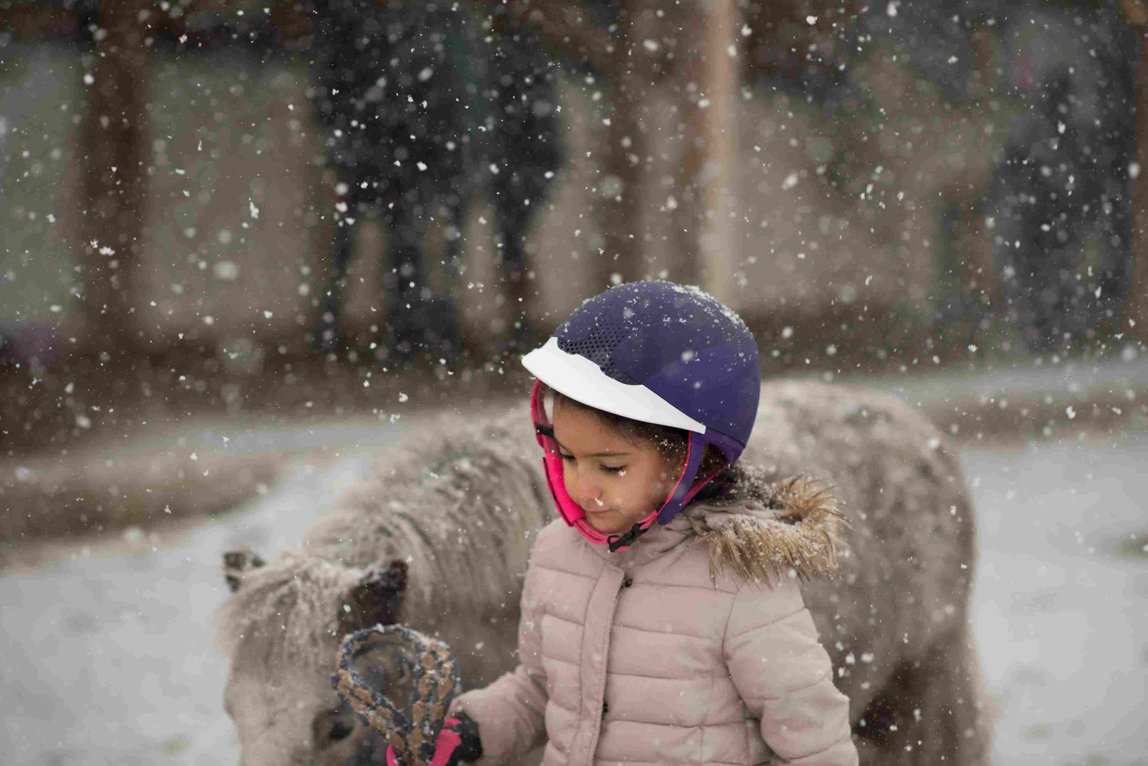 Una niña y un pony en un día de nieve.