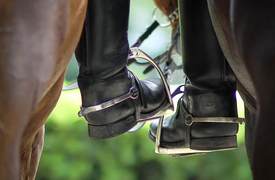 Closeup of horseback riders' boots in stirrups
