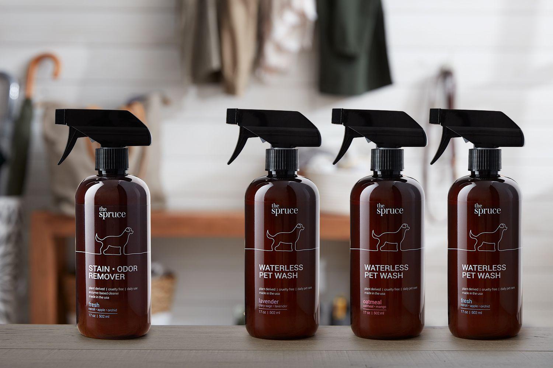 Bodegón de cuatro botellas ámbar de quitamanchas y olores y lavado de mascotas sin agua
