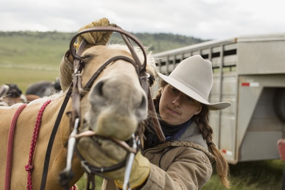 Female rancher placing bridle and bit on horse