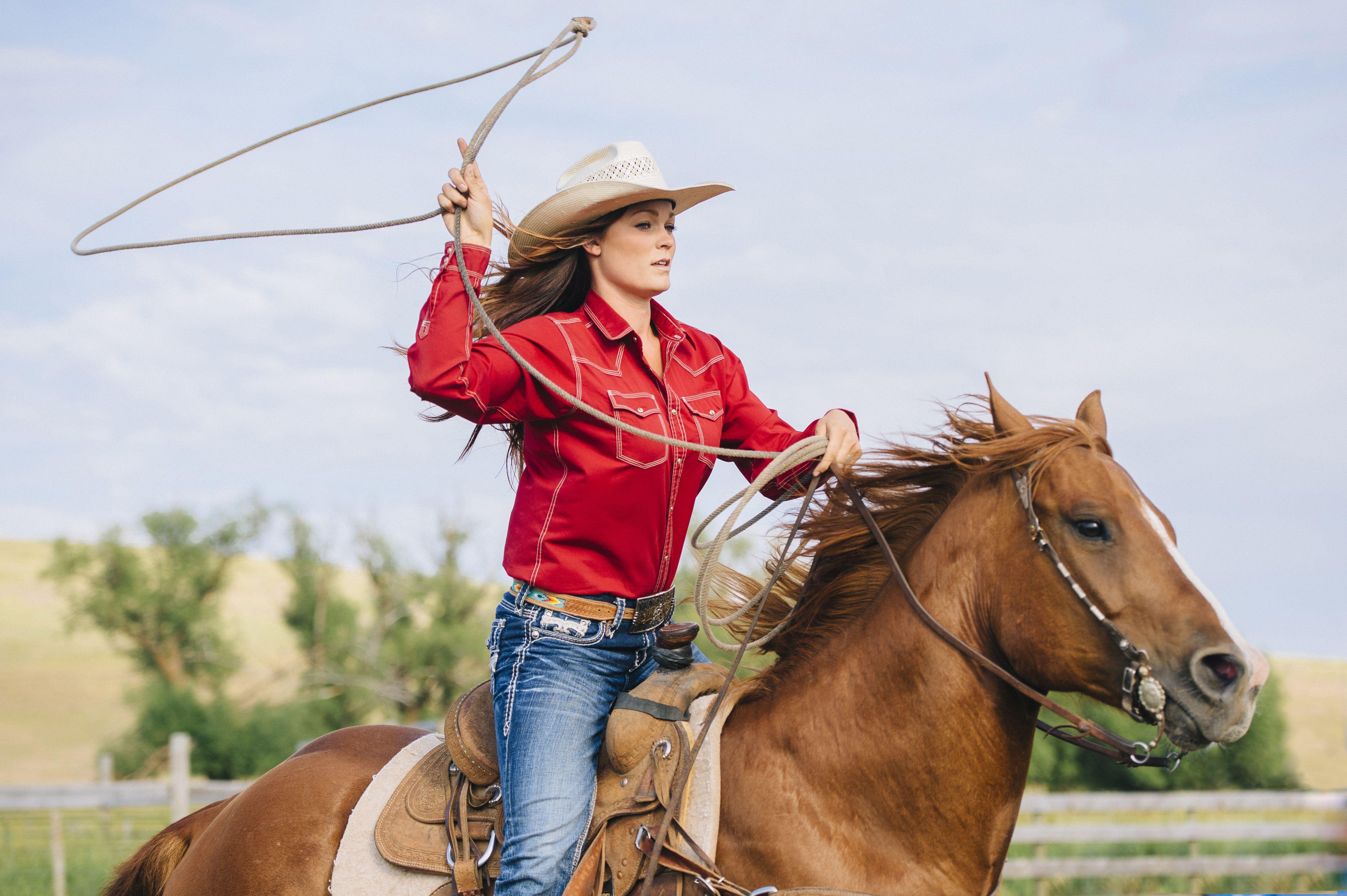 Caucasian cowgirl throwing lasso on horseback
