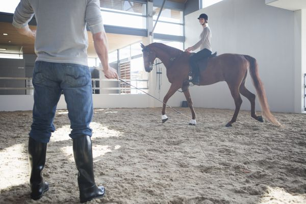 Female horseback riding with instructor in indoor paddock