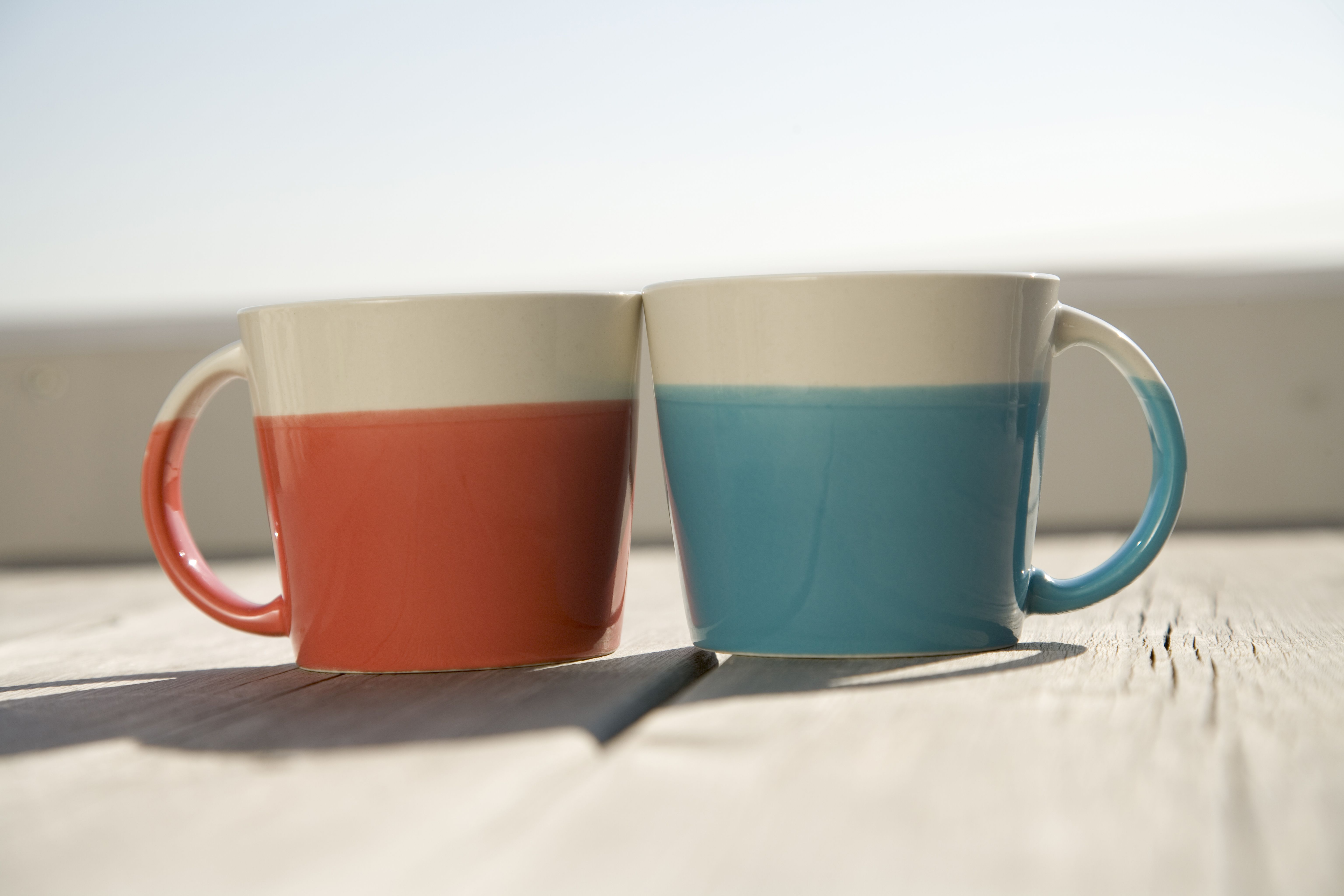 Two coffee cups resting on a table.