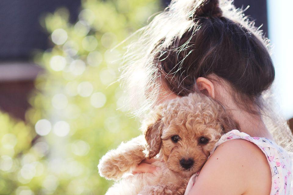 Girl cuddling her puppy dog