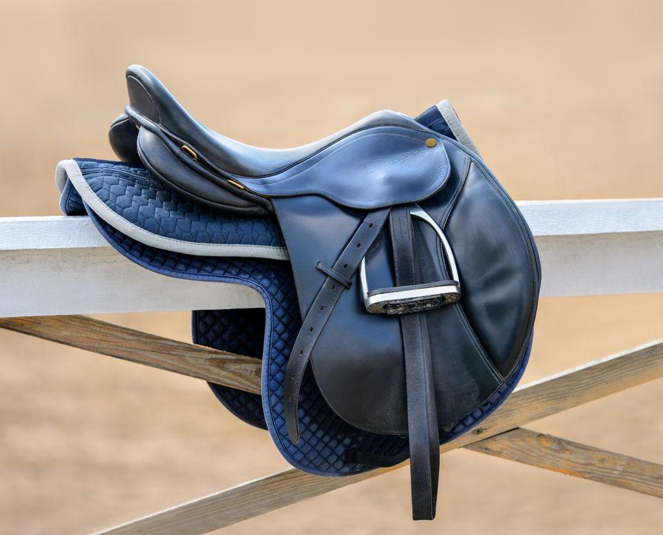 Black English saddle hanging on fence near stables.