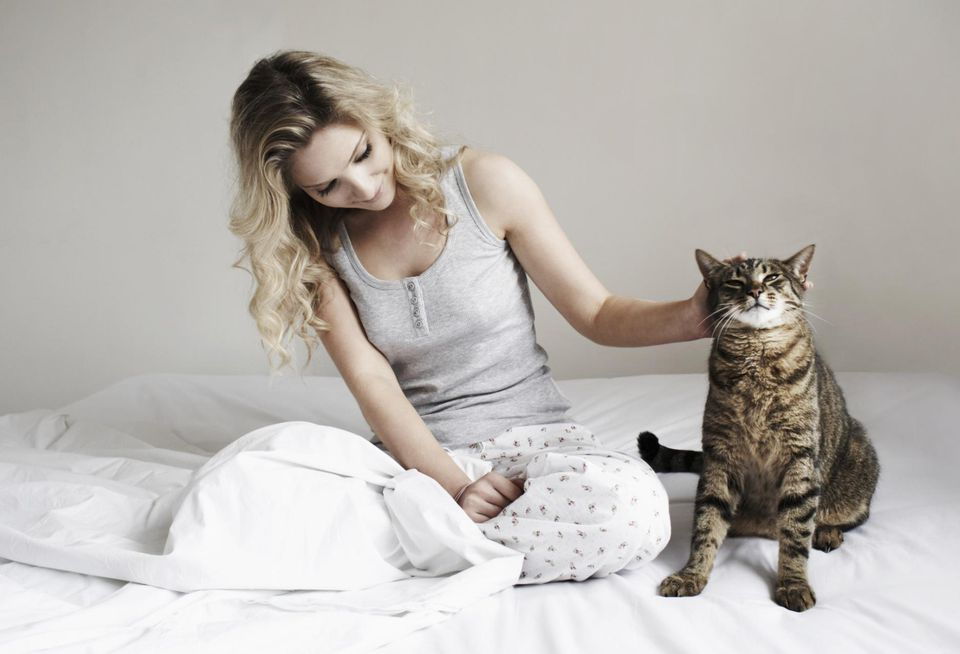 Woman sitting on bed stroking her cat