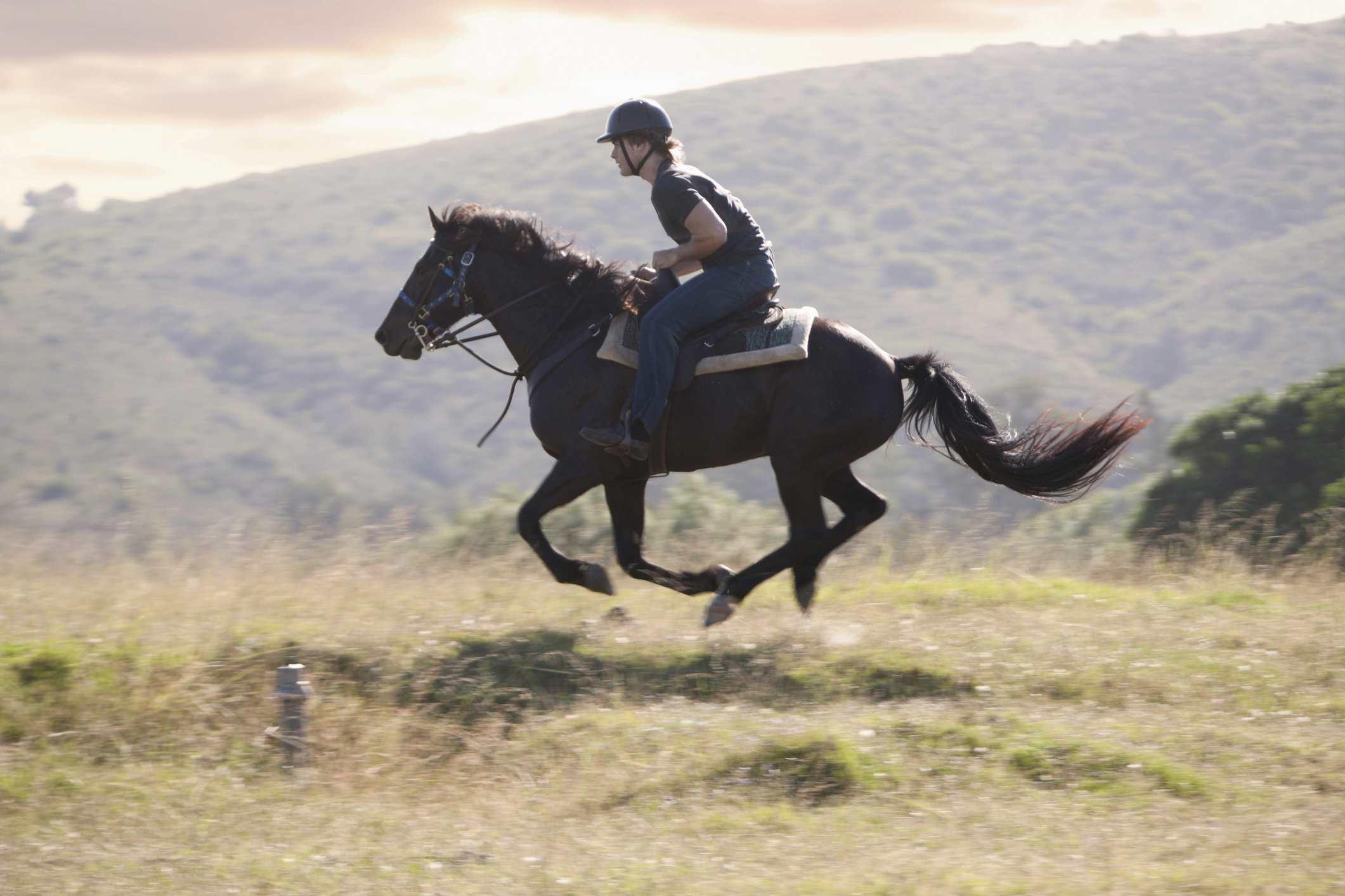 Man riding horse leaning forward