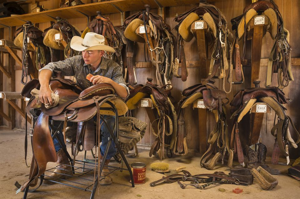 Man cleaning a leather saddle
