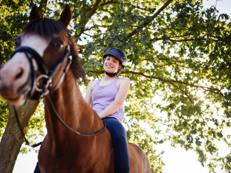 Girl horserider looking lovingly at the horse she is on