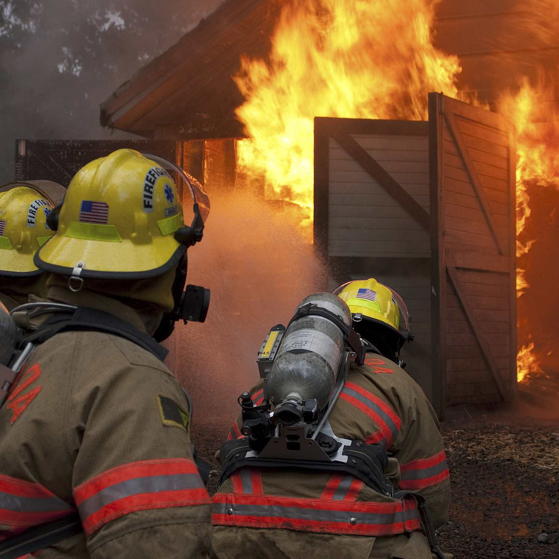 Fire fighters approaching blazing barn door