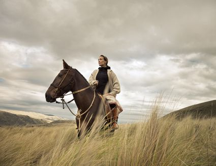 content woman sitting on horse in highland