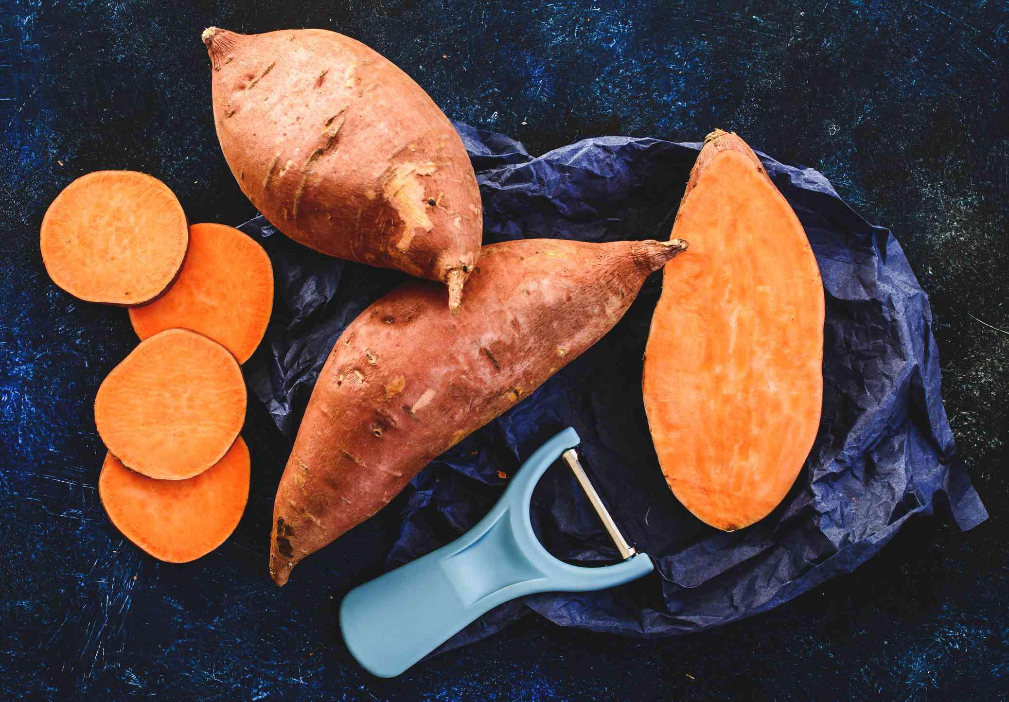 Birds eye view of two whole sweet potatoes and some sliced sweet potatoes next to peeler.