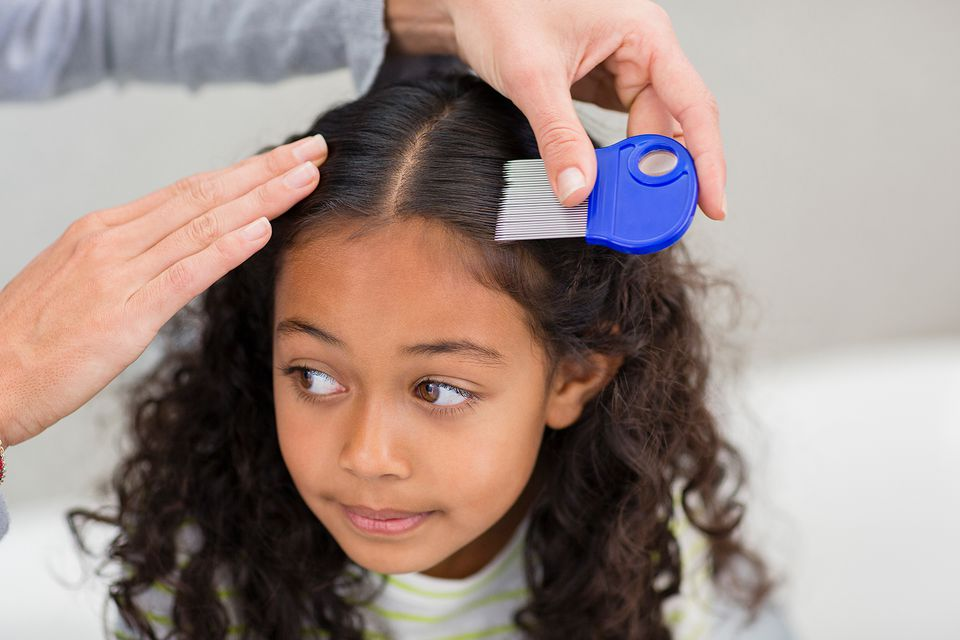 Mother using lice comb on daughters hair