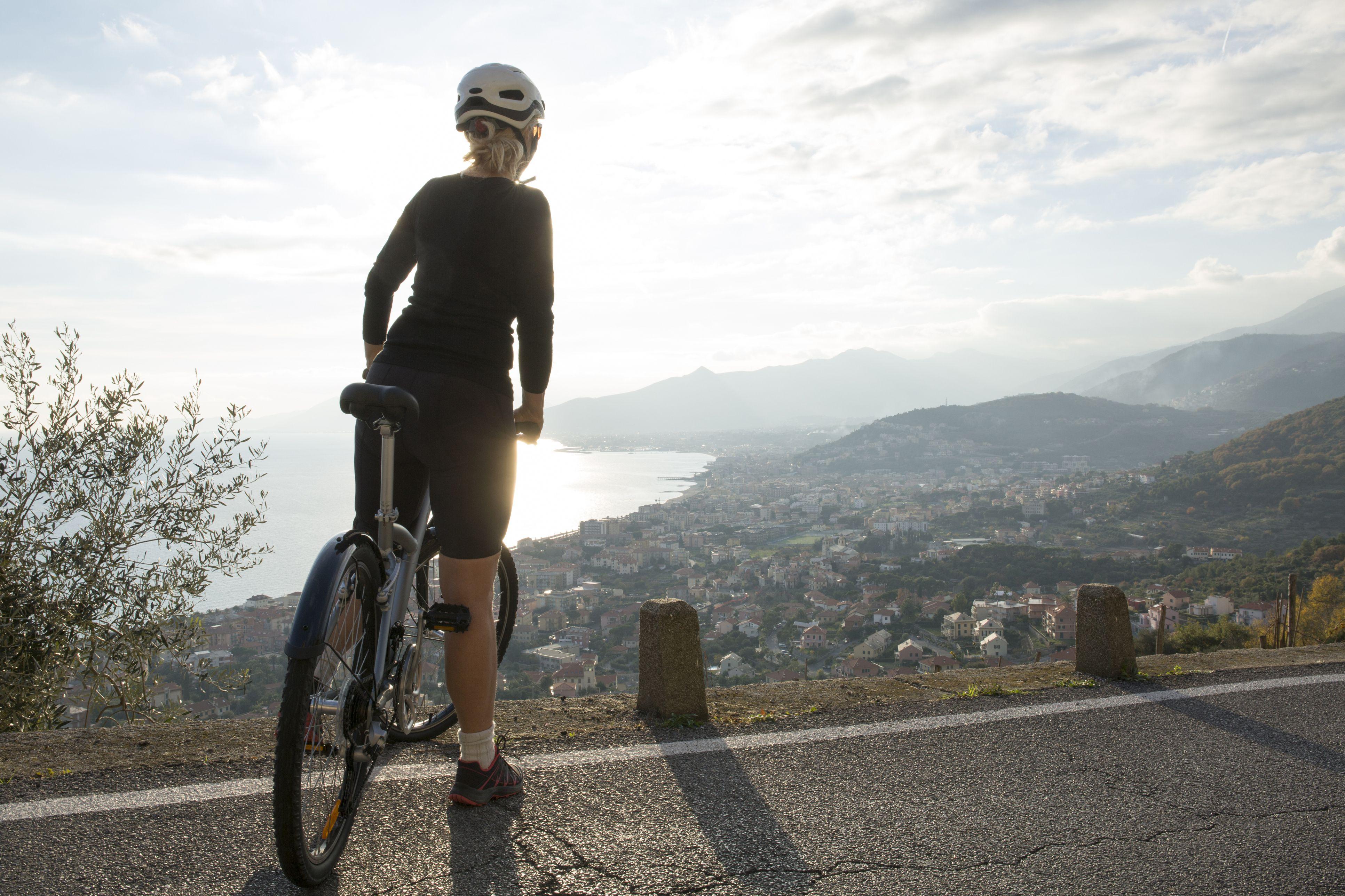 Una mujer se detiene con una bicicleta en una vista panorámica.
