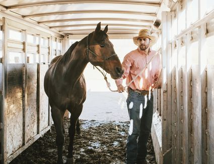Man loading horse into stall in trailer