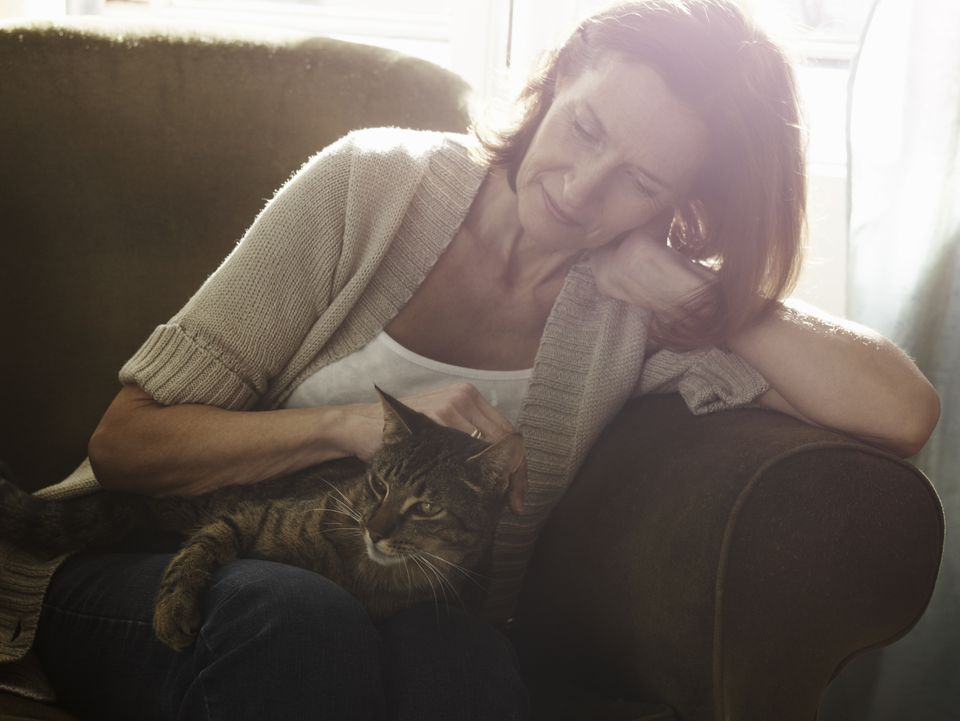 Portrait of mature woman stroking cat