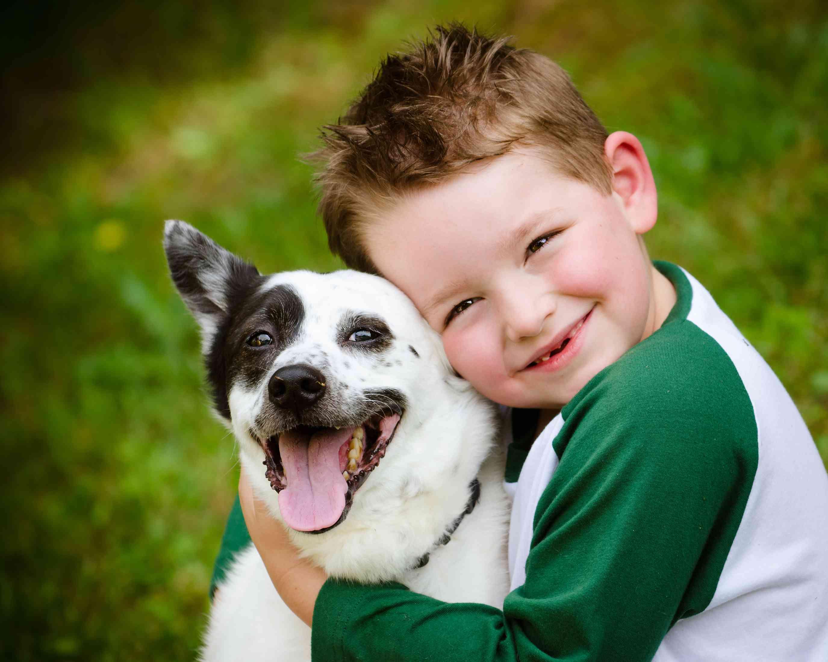 Joven abrazando perro feliz con manchas