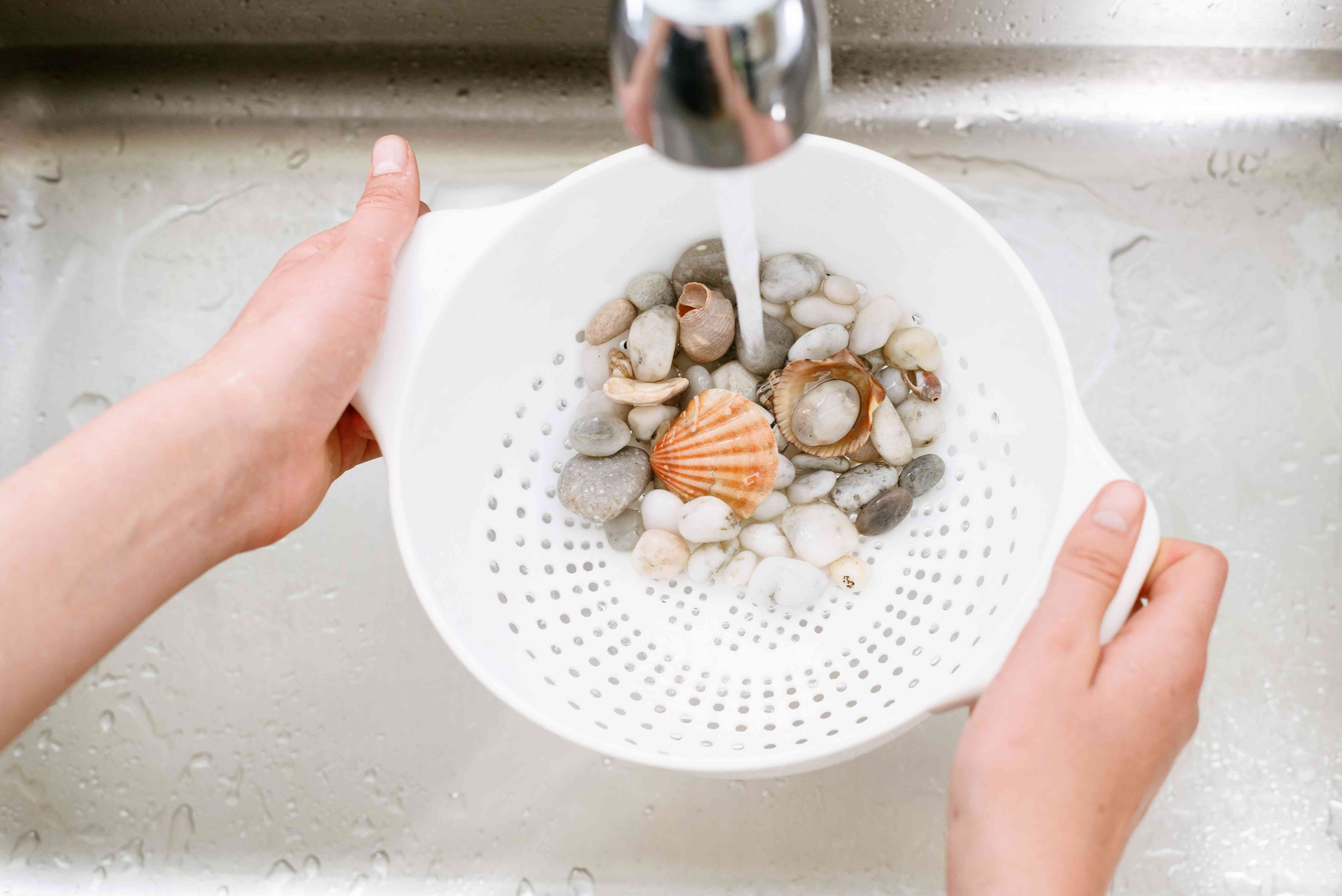 Fishbowl decorations rinsed under running faucet with warm water and white strainer