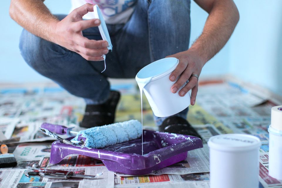 Man pouring paint into roller tray