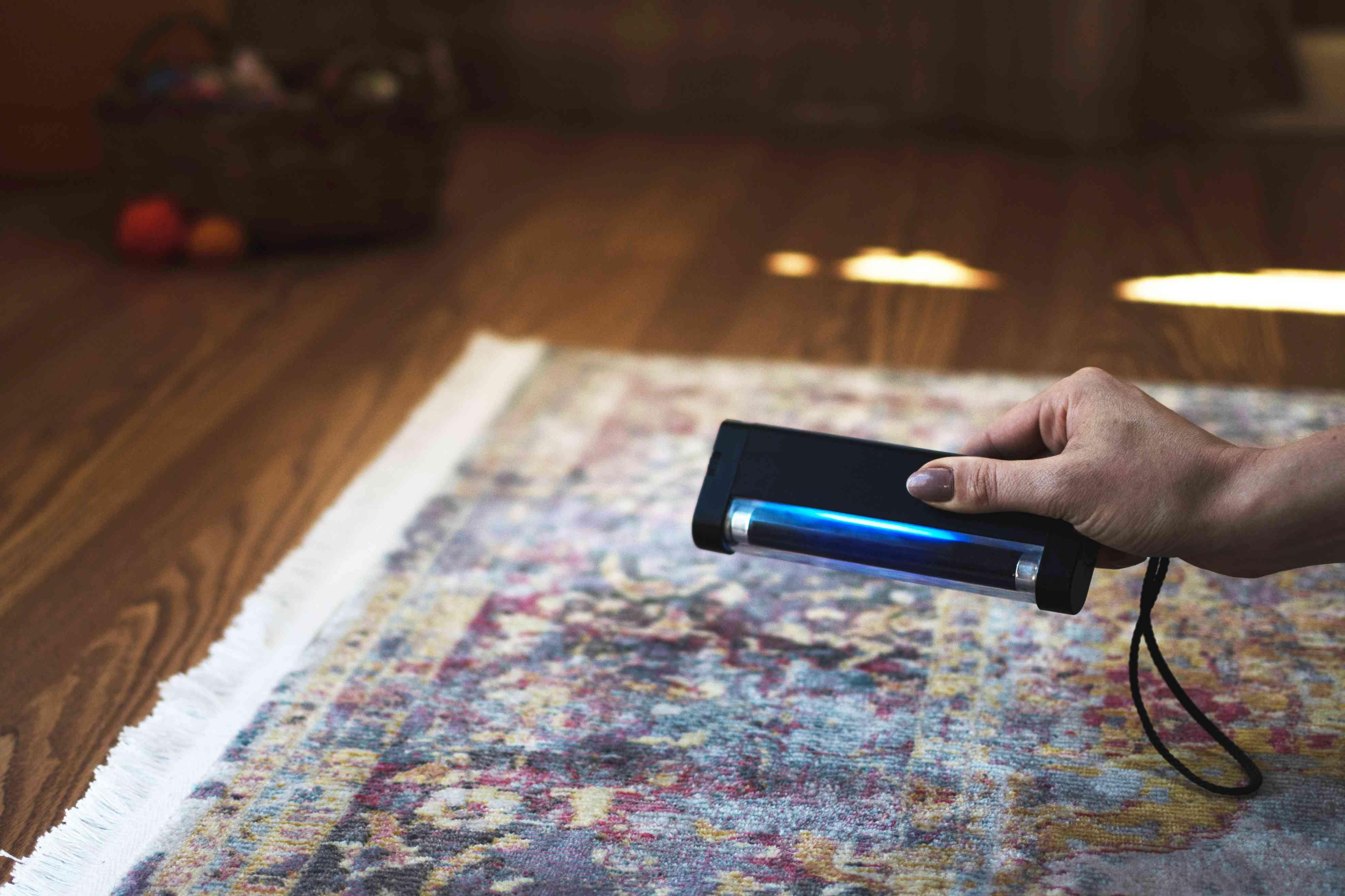 Black light hovering over patterned rug to find hidden stains