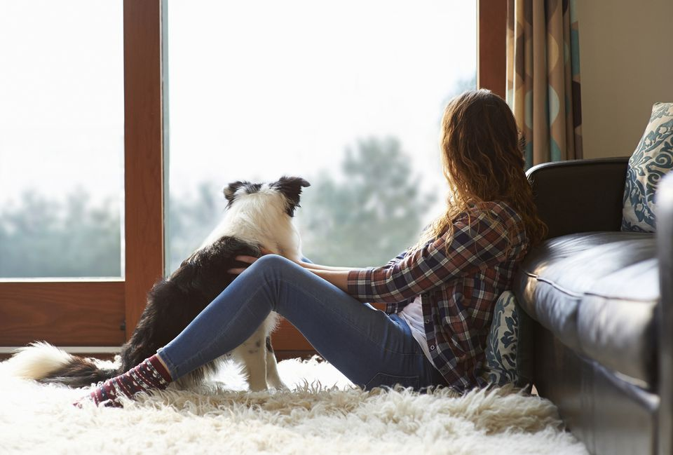Woman and dog sitting on a furry rug