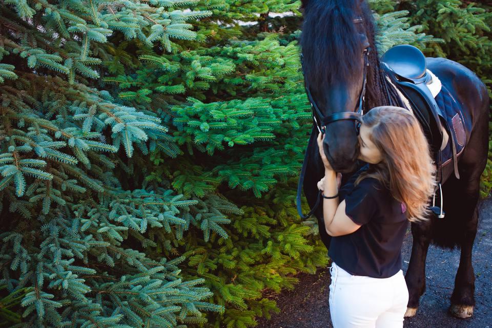 Joven mujer besando a caballo mientras está de pie junto a los árboles