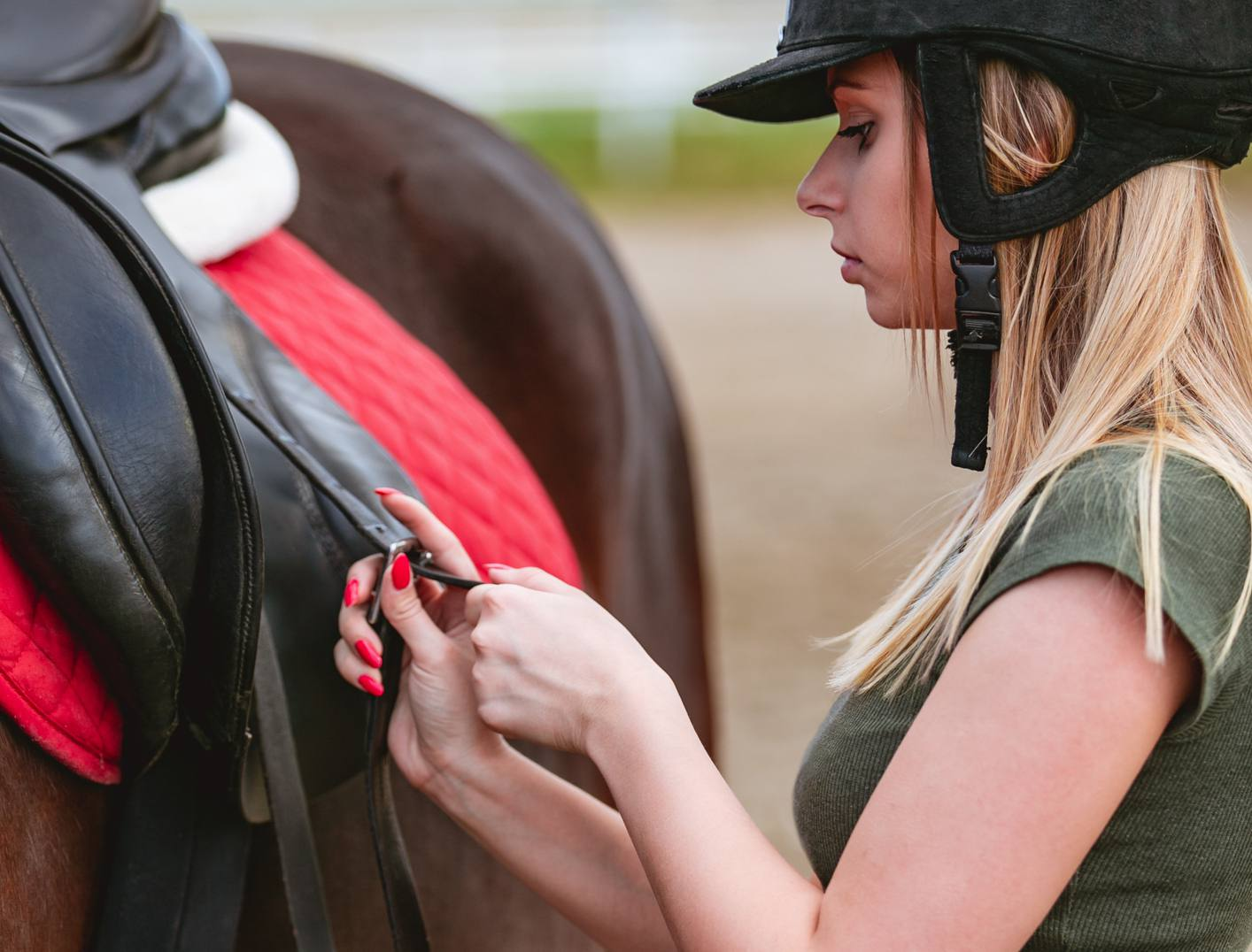 Woman cinching strap on saddle of horse