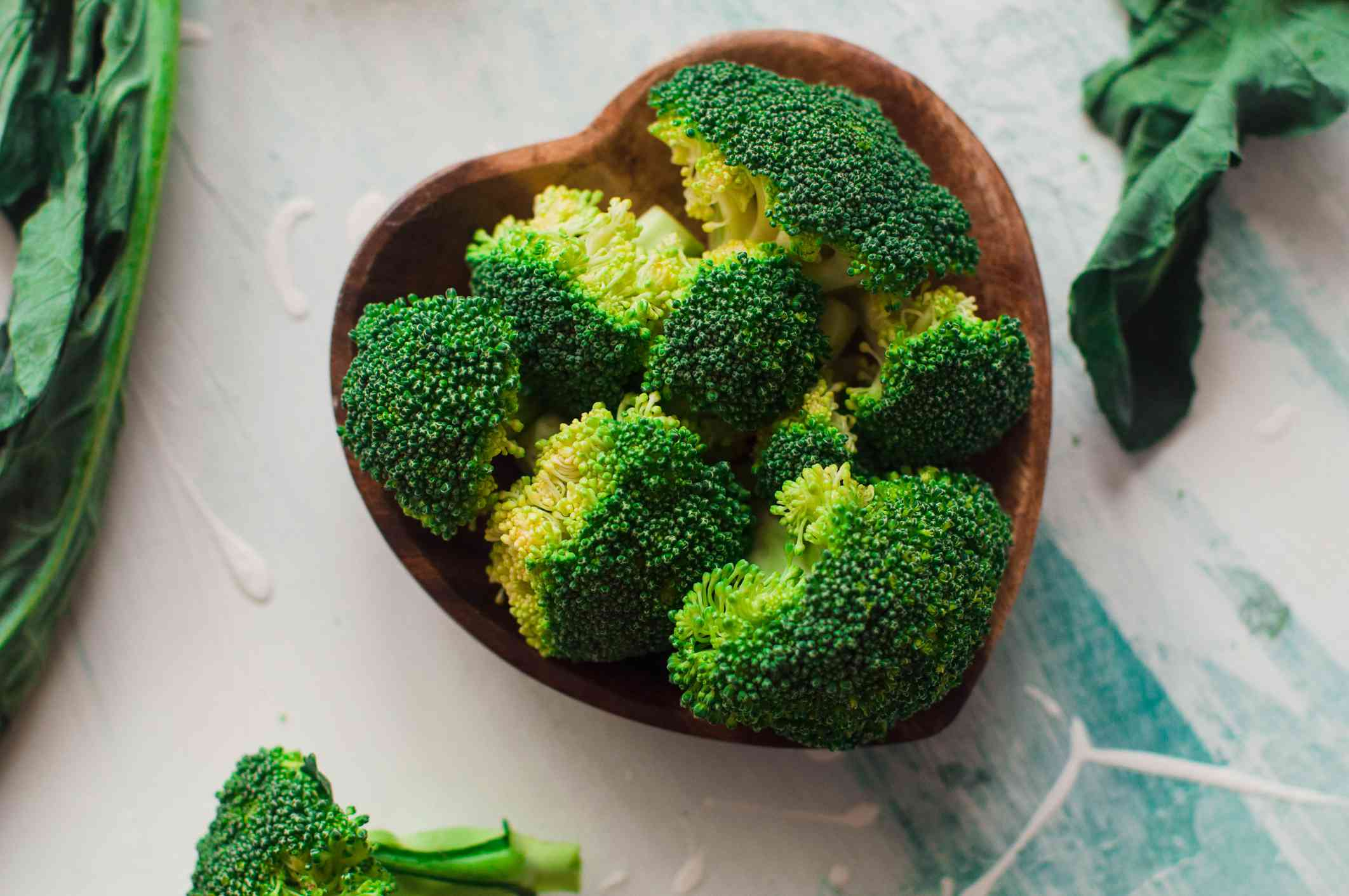 Heart shaped wood bowl filled with broccoli florets.