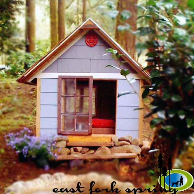A whimsical dog house in the woods.