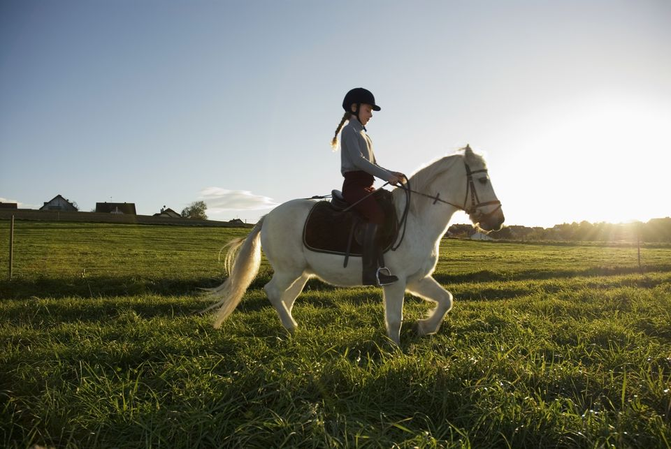 Girl riding a pony, side view