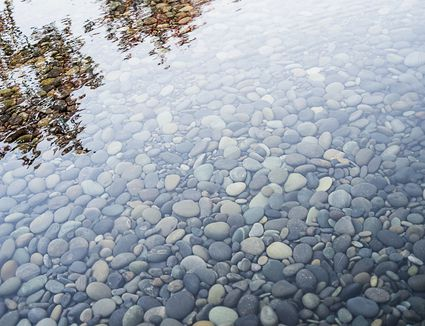 Pebbles on a river bed. Reflections and ripples on the surface.