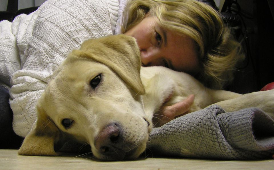 A woman cuddling with a dog