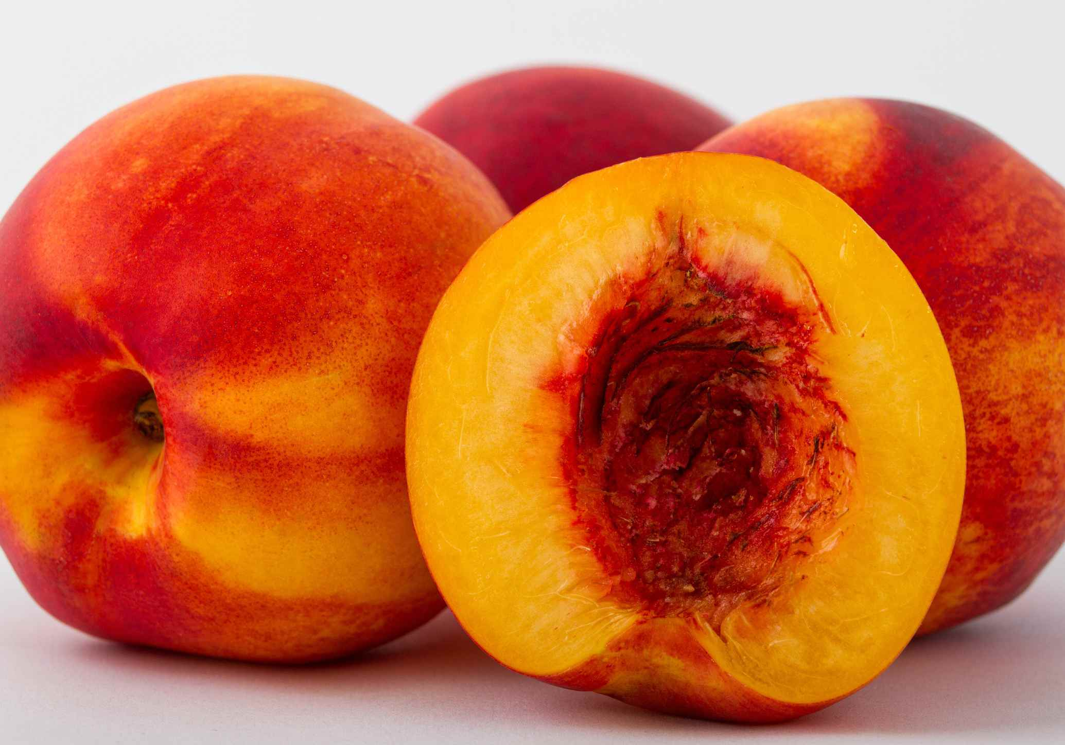 Peaches with one cut open and the pit removed.