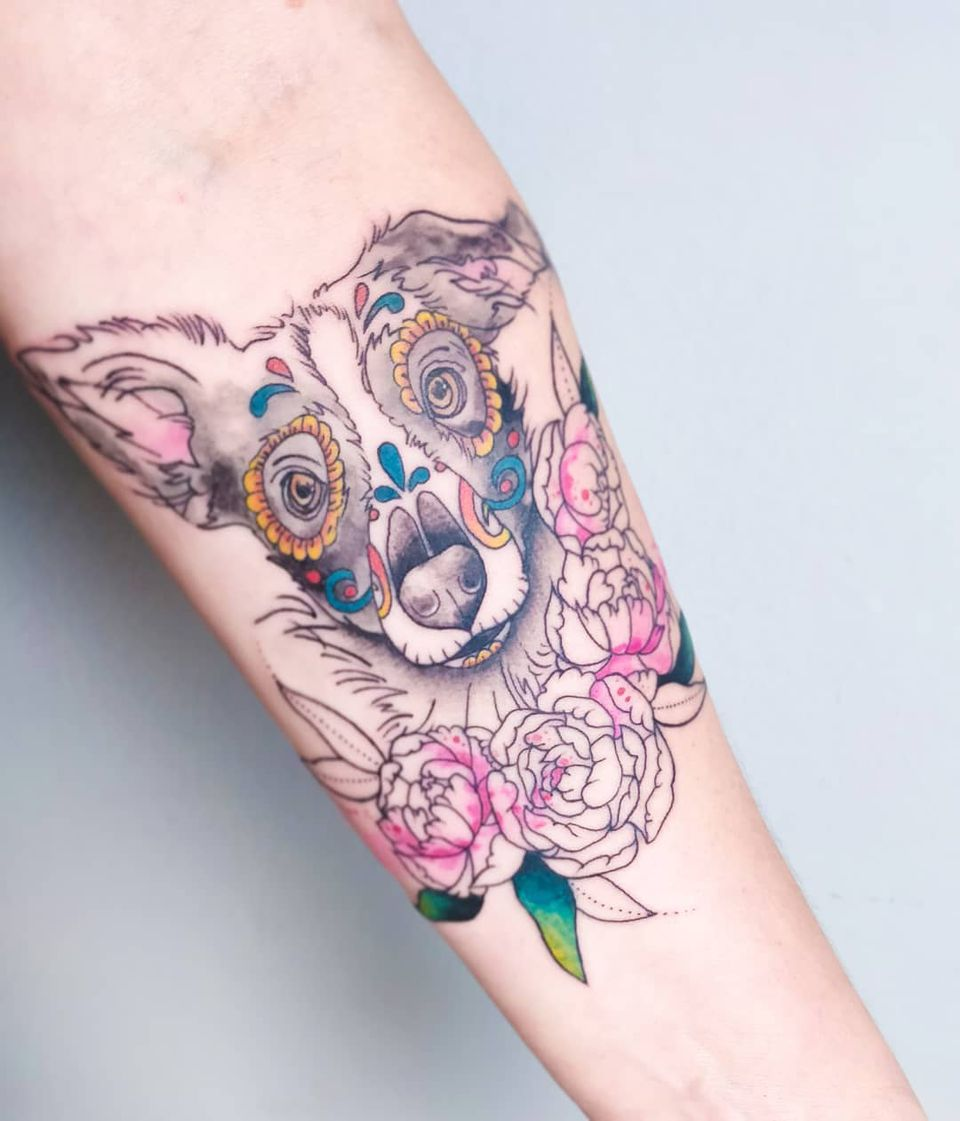 A sugar skull-style tattoo of a dog.