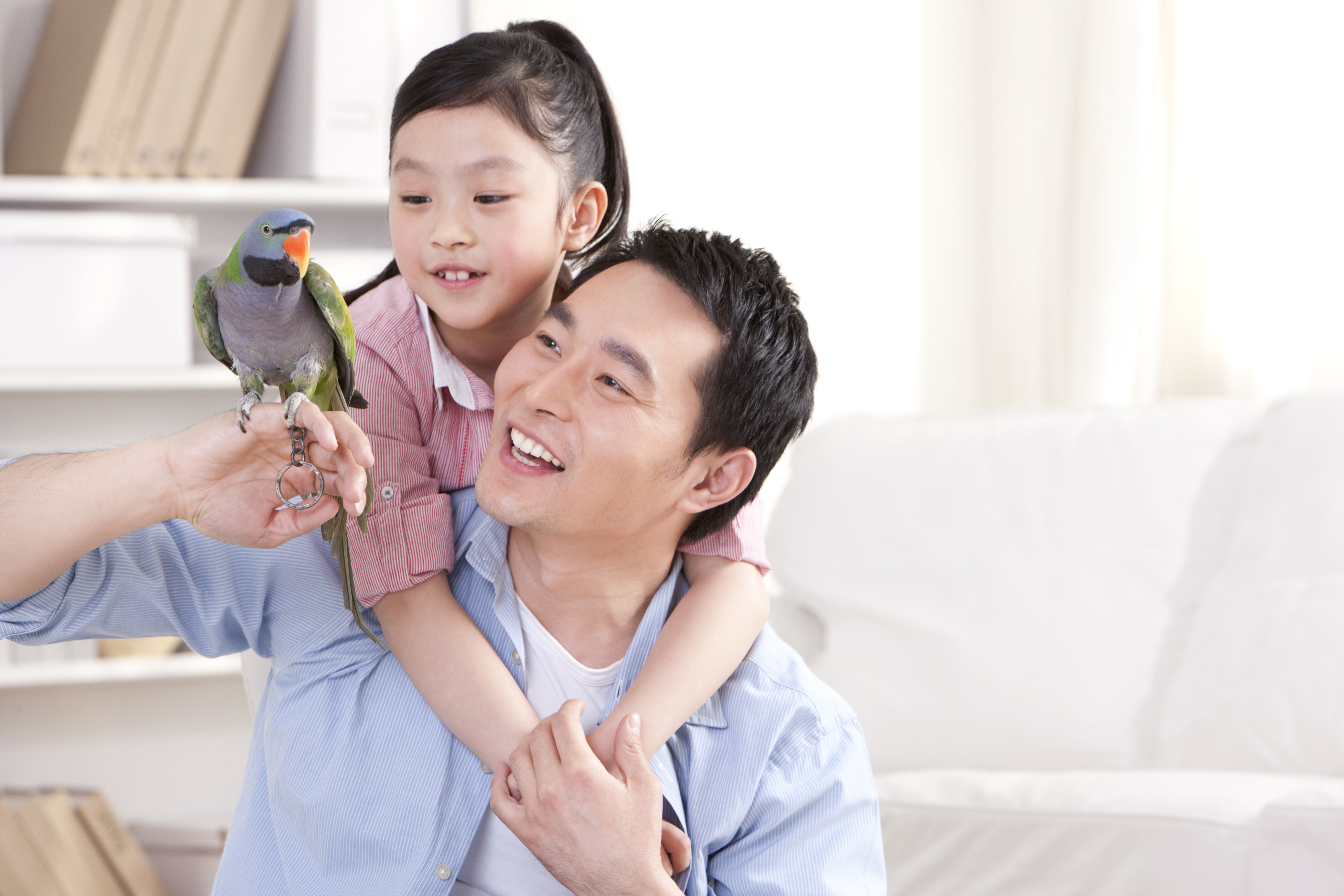 Father and daughter playing with a pet parrot