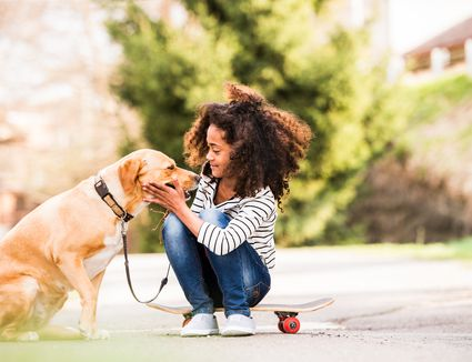 Girl outdoors on skateboard with her dog
