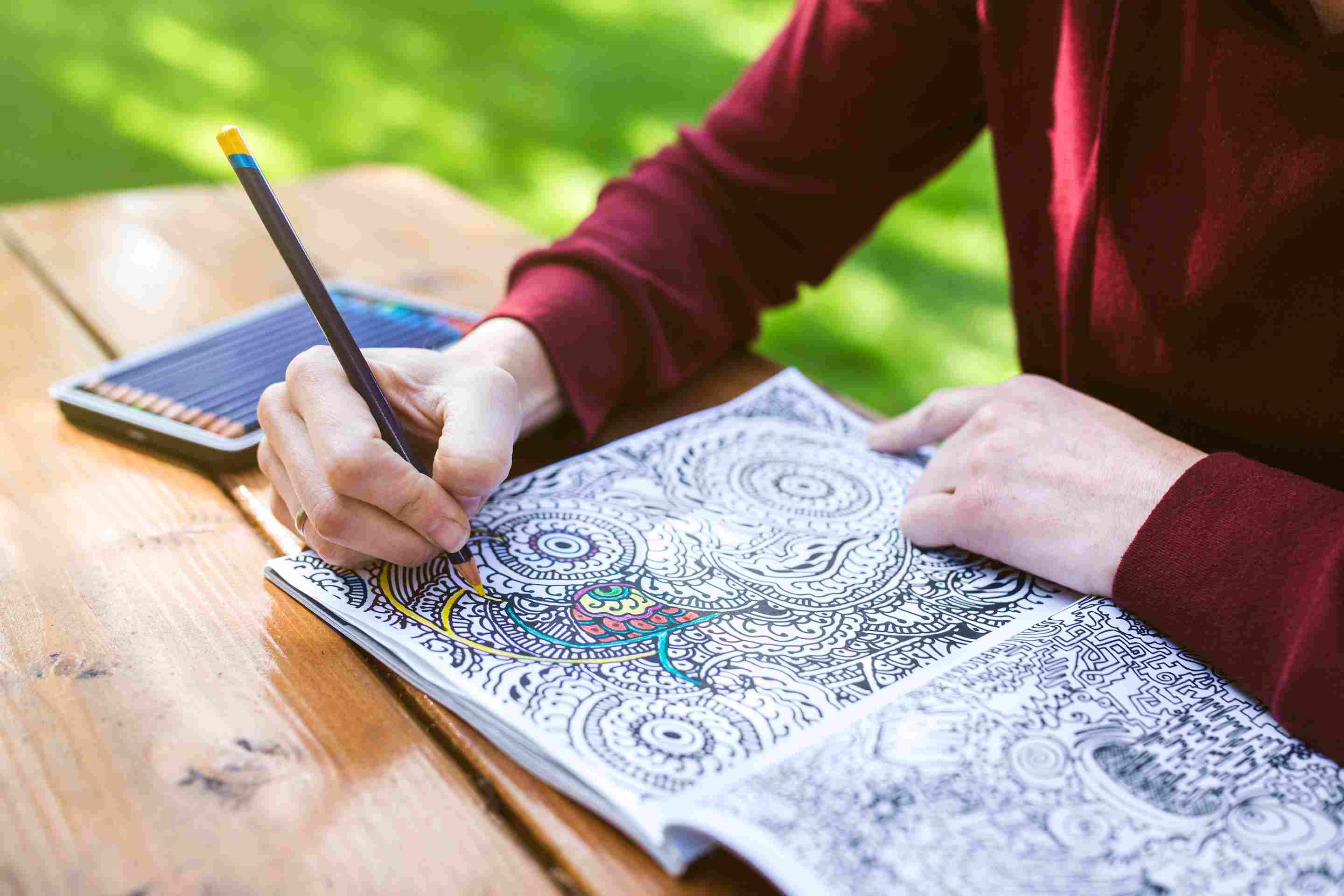 Woman using a coloring pencil to color an intricate coloring book.