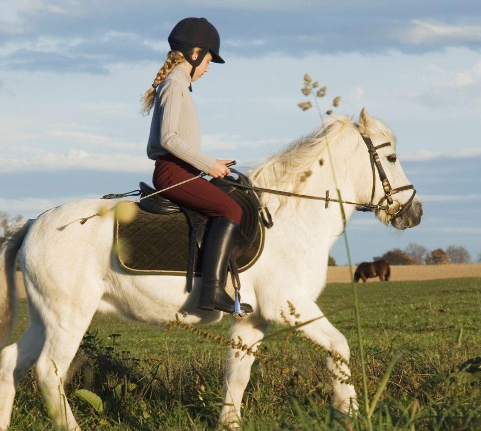 Girl riding white pony.