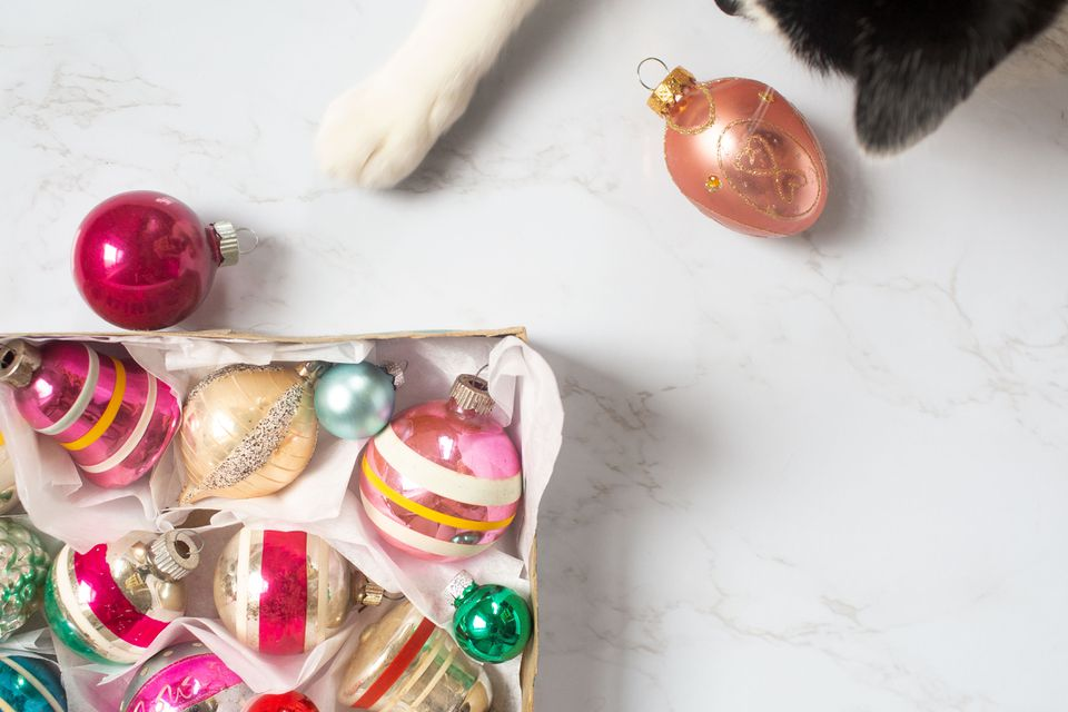 a cat playing with Christmas ornaments