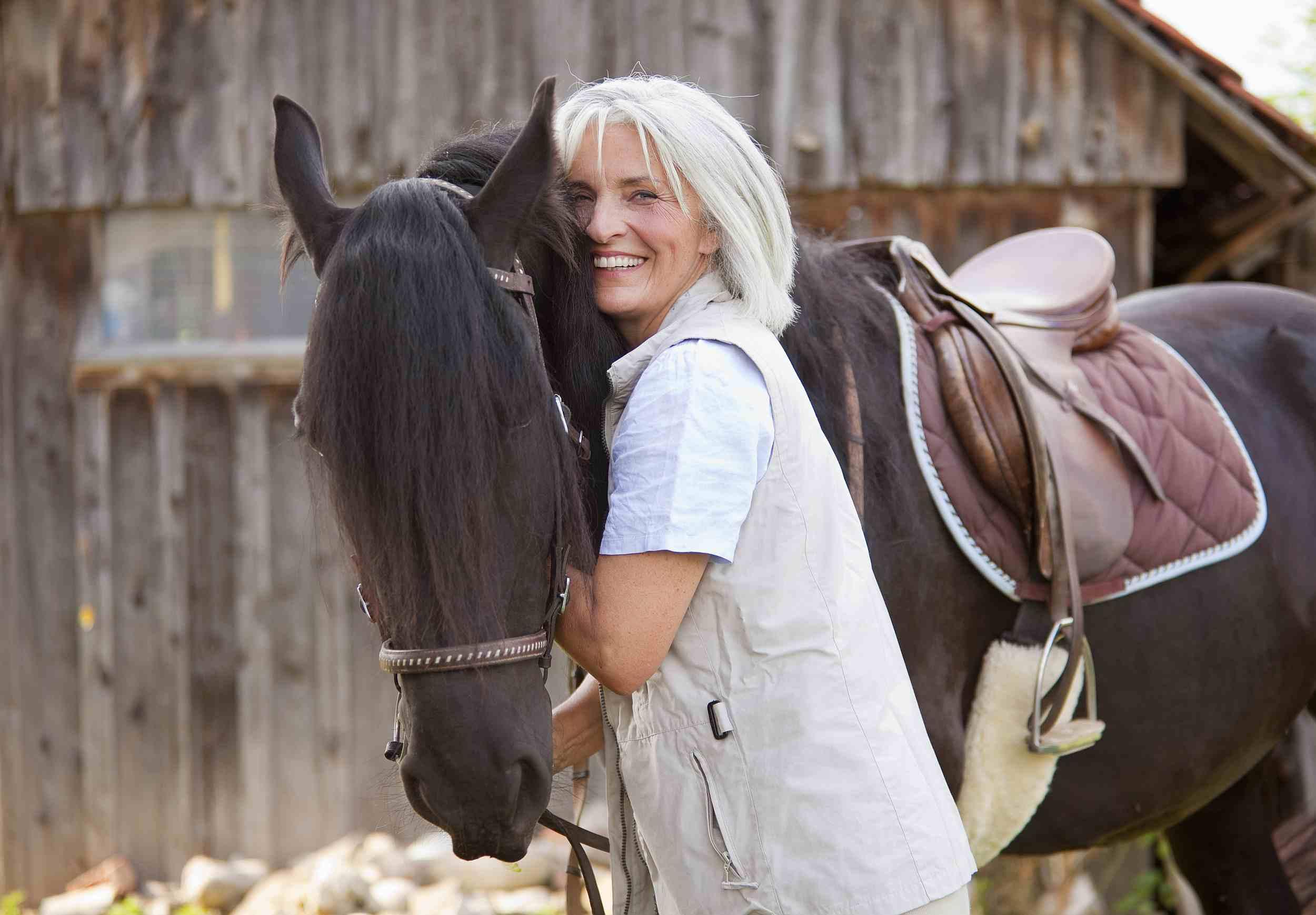 Mujer madura abrazando a caballo