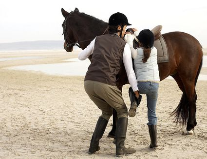 Woman helping child mount horse