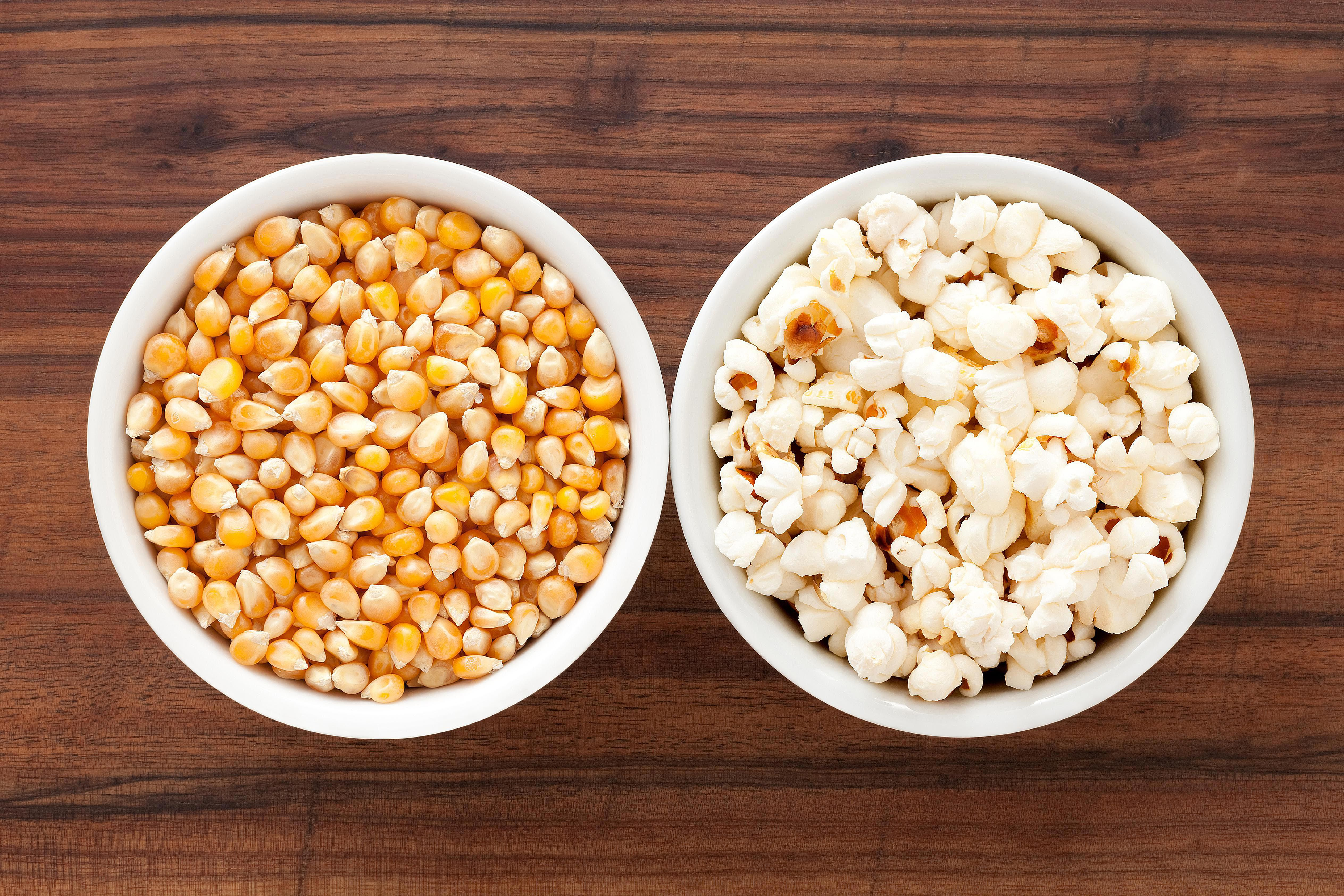 A bowl of corn and a bowl of popcorn