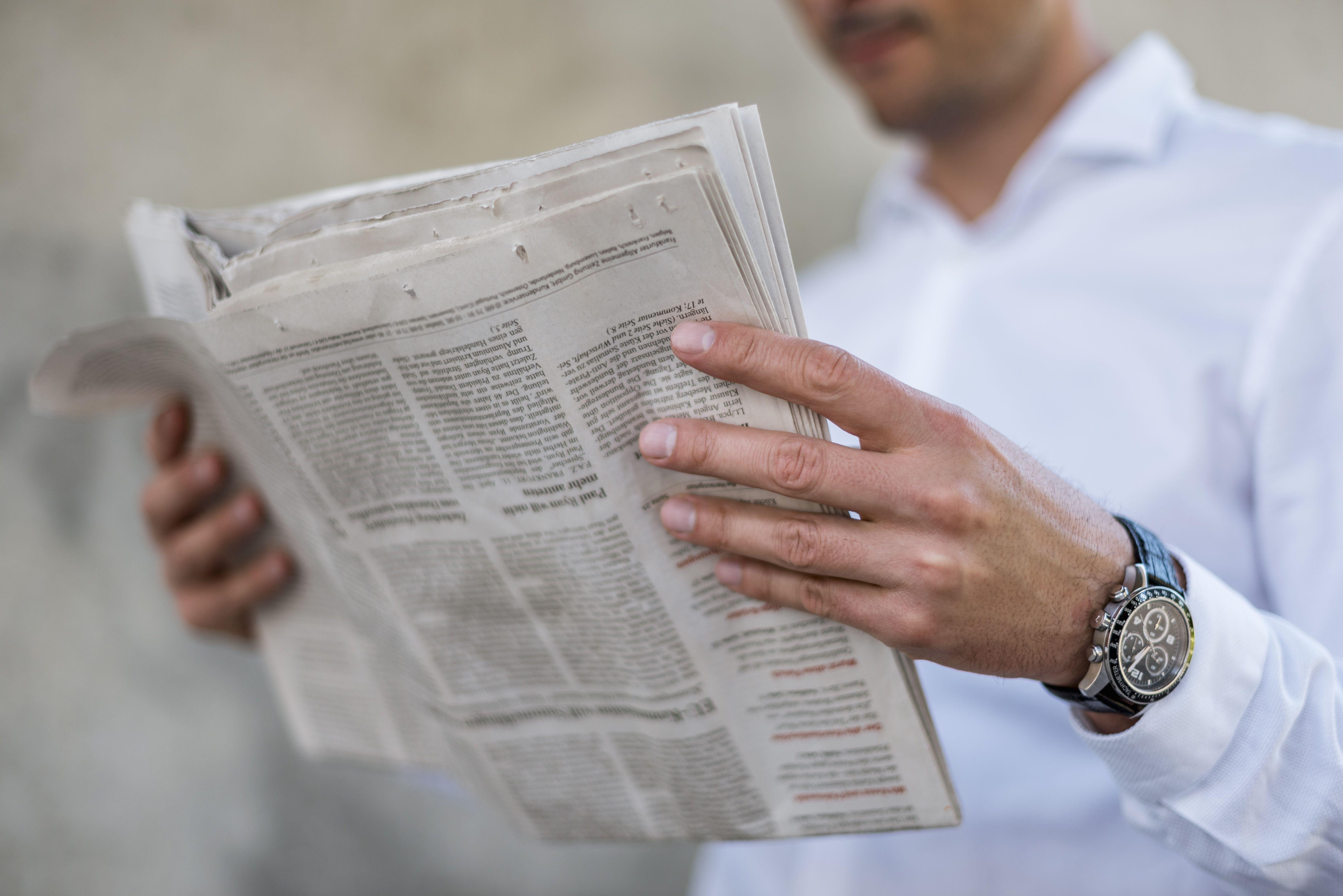 Close-up of businessman reading newspaper