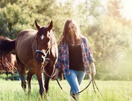 Woman walking with pet horse