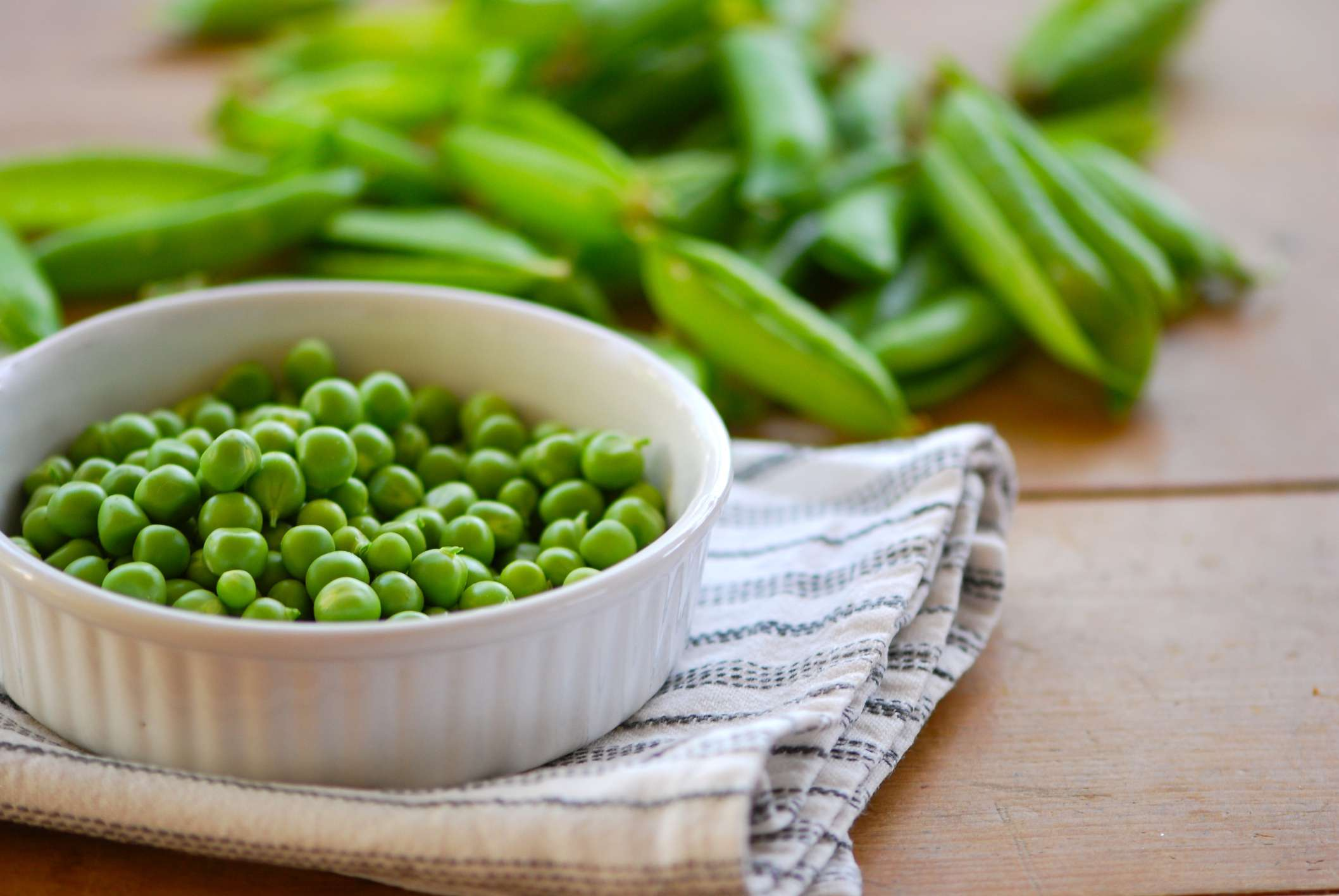 Bowl of shelled peas next to peas in shell.