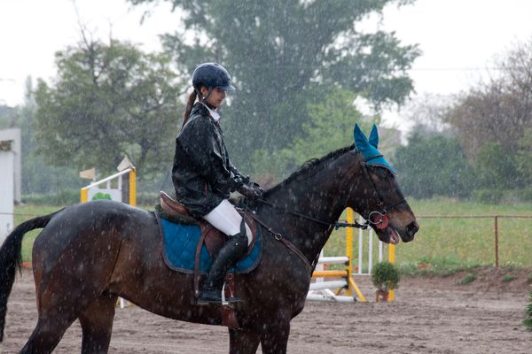 Girl riding horse in the rain